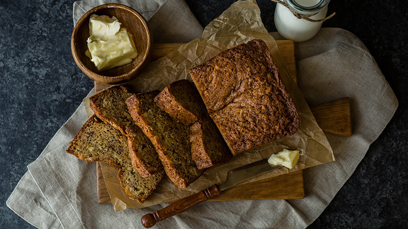 Banana bread partially sliced next to a butter knife and milk