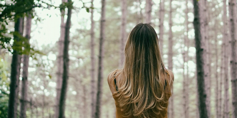 Woman standing in a forest looking up towards heaven facing away from camera