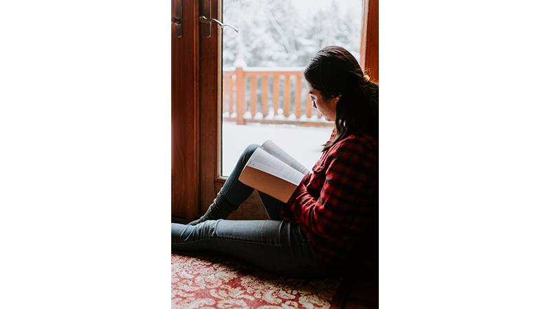 Girl sitting by window reading in winter