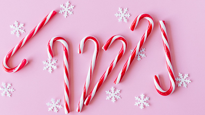 Peppermint Candy Canes on a pink background with little snow flake decorations