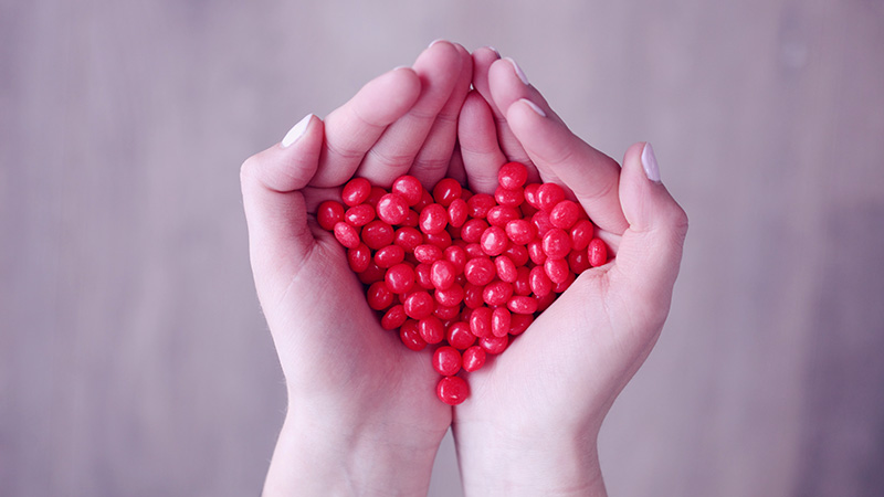 Red hot cinnamon candys held in two hands in a heart shape