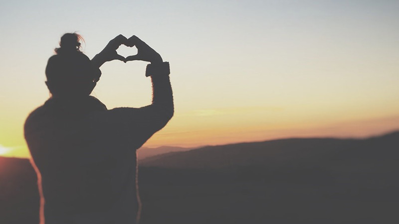 Girl shaping a heart with her hands dark against the sunset over mountains
