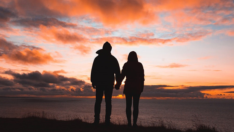 woman and man holding hands on the beach watching the sunset sky in many colors